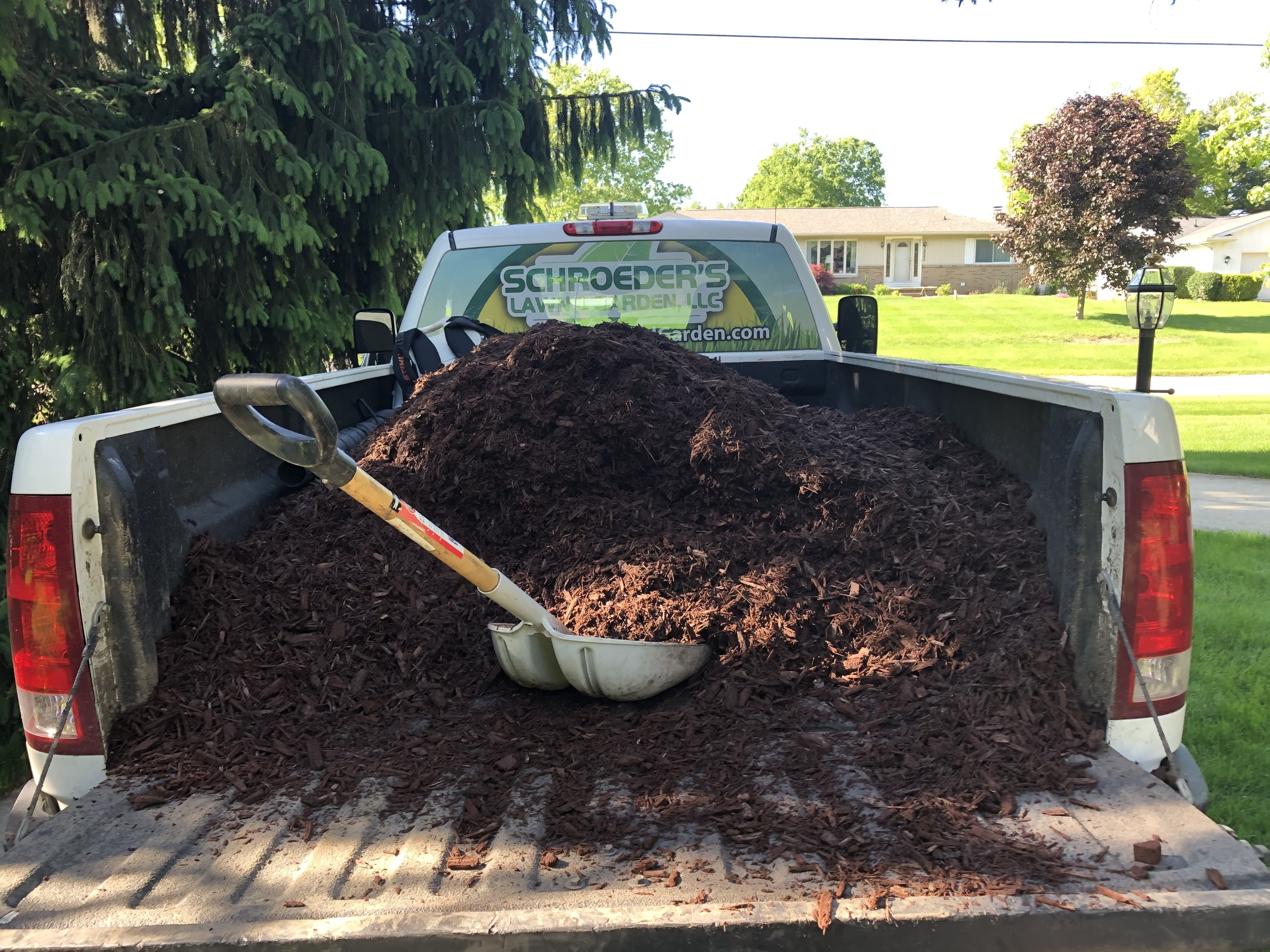 New mulch being laid in landscape bed at Lenawee home.